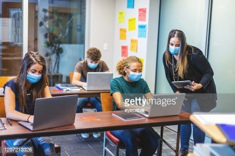 Female high school teacher offering assignment assistance and three students in classroom setting wearing face masks.
